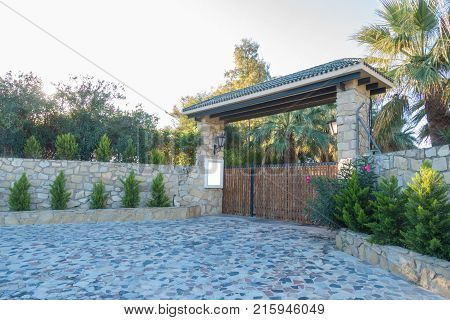 Mock up near the gate to the private house yard. Wooden gates and a high stone fence.