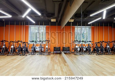 Room with indoor cycling machines and climb ropes in fitness studio.