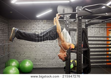Man doing exercises on horizontal bar in gym hall.
