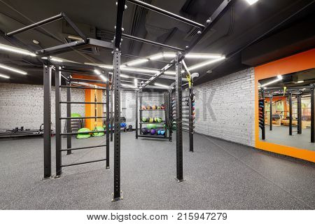 Room in fitness studio with different sports equipment, horizontal bars, ladders, balls, barbells.