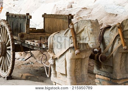 Ming Dynasty wooden carriage pulled by stone horses.