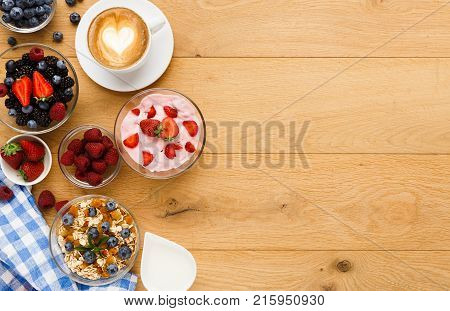 Tasty breakfast with light greek yogurt, muesli, fresh organic berries and latte coffee. Low fat morning meals and healthy start of the day. Detox and diet concept, top view, copy space