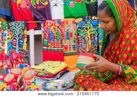 KOLKATA WEST BENGAL INDIA - DECEMBER 3RD 2016 : Colourful handicrafts are being prepared by middle aged woman for sale in Kolkata in handicrafts trade fair. It is rural Industry in West Bengal.