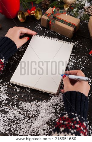 Holiday decorations and blank white notepad for wishlist on rustic wooden table with gift boxes and fir tree branch sprinkled with snow. Preparing for winter holidays and letter to Santa concept.
