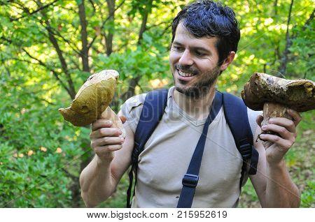 Portrait of man holding two giant porcini mushrooms. Happy man picking big boletus edulis or cap mushrooms in forest