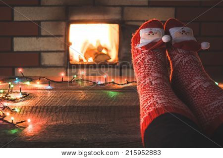 Feet in woollen red socks by the fireplace. Female relaxes by warm fire and warming up her feet in christmas socks.