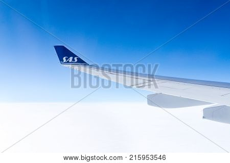 LOS ANGELES USA - AUGUST 17 2017: View to SAS airplane wing during flight through window from cabin. Scandinavian Airlines is the largest airline in Norway Sweden and Denmark. Editorial.