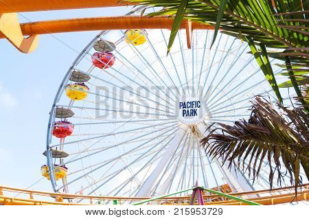 LOS ANGELES USA - AUGUST 18 2017: The ferris wheel in Pacific Park framed by palm trees. Pacific Park is the only amusement park in Los Angeles without an admission fee. Editorial.