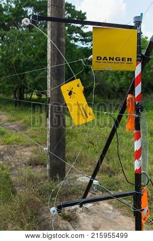 The yellow warning plate and electric fence protecting dwellings of people from large wild animals in the jungle.