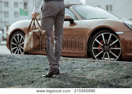 Cool man beautiful model outdoors, city style fashion. A handsome man model walking in the city center next to some cars. urban setting. The young boy as trendy, modern clothing with bag.