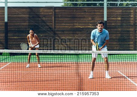 Lets play a game! Beautiful young couple playing tennis on the tennis court.