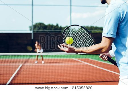 Exciting competition. Rear view of young couple playing tennis on the tennis court.