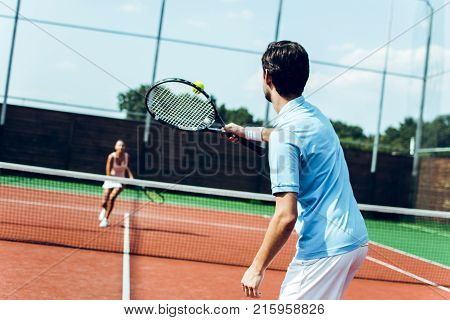 Exciting game. Rear view of young couple playing tennis on the tennis court.