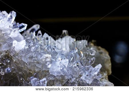 Rock crystal stone, blueish look, on a black background, natural phenomenon, closeup photograph. Also known as mountain crystal.