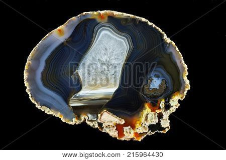 A cross section of the agate stone. Multicolored silica bands colored with metal oxides are visible. Horizontal agate filled with quartz. Origin: Rudno near Krakow Poland.