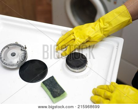 Female hands wearing protective gloves cleaning a gas stove top