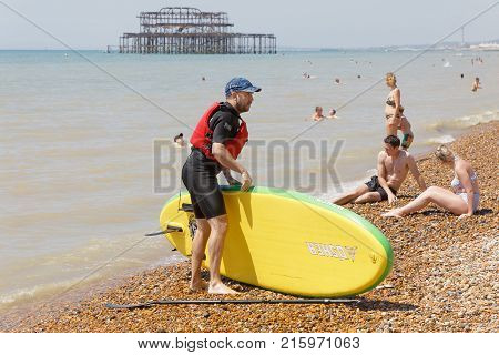 BRIGHTON GREAT BRITAIN - JUN 17 2017: Man with a surfboard and sunbathing people on the Brighton beach West pier in the background. June 17 2017 in Brighton Great Britain