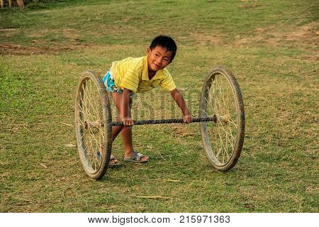 Vang Vieng, Laos - November 25: Unidentified Boy Plays With Set Of Wheels On November 25, 2011 In Va