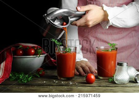 a woman pours tomato juice from  the juicer