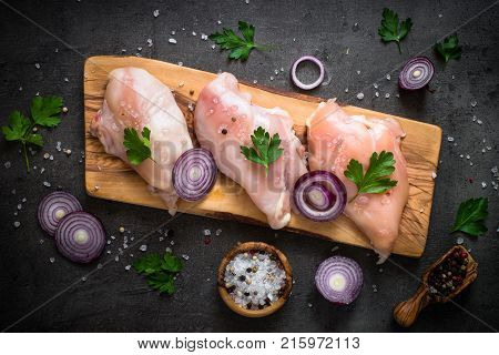 Raw chicken fillet meat on cutting board. Ready for cooking. Fresh Chicken breast Raw Meat steak. Top view on black stone table.