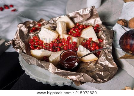Cheese, red currants. French cuisine for a buffet table