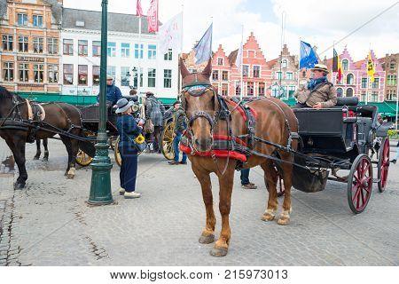 Bruges, Belgium - April 17, 2017: Horse carriage on Grote Markt square in Belgian city of Bruges.