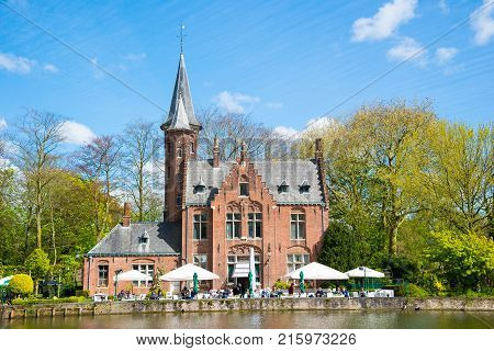 Bruges, Belgium - April 17, 2017: Minnewater castle at the Lake of Love in Bruges, Belgium