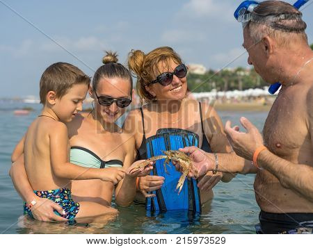 Portrait smiling family playing with the crab in the sea ocean. Positive human emotions feelings joy. Funny cute child making vacations and enjoying summer.