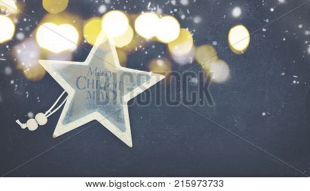 Merry Christmas star on black wooden background with copy space and snow banner
