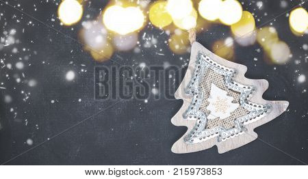 Decorative christmas tree on black wooden background with snow banner