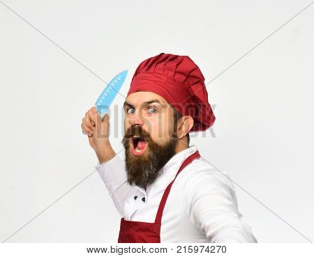 Cook With Wild Face In Burgundy Apron And Chef Hat.