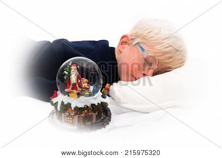 Waiting for Santa Claus: Handsome four year old boy sleeping next to Christmas music box and snow globe on white background