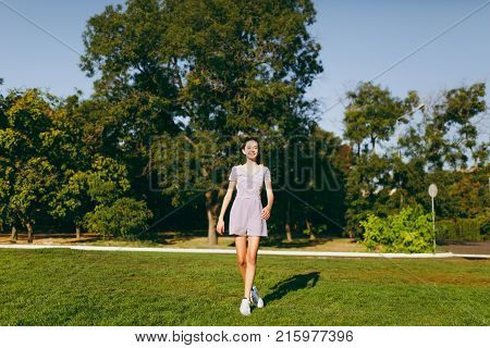 Young Pretty Girl With Long Brown Hair Dressed In Light Clothes Staying On Green Lawn Grass In The P