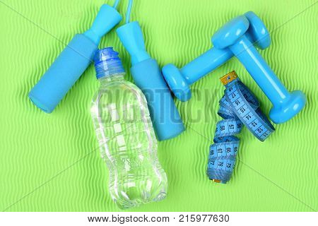 Dumbbells, Cyan Jump Rope And Water Bottle On Green Background