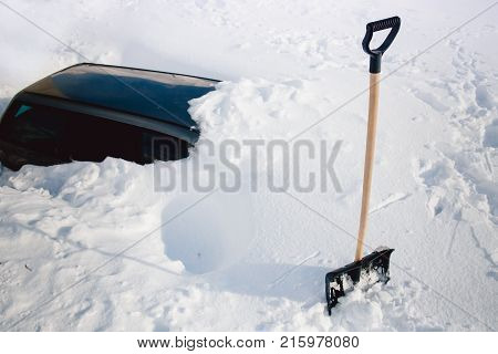 Shovel in the snow, in the background the car is covered with snow. Winter, abnormal snowfall.