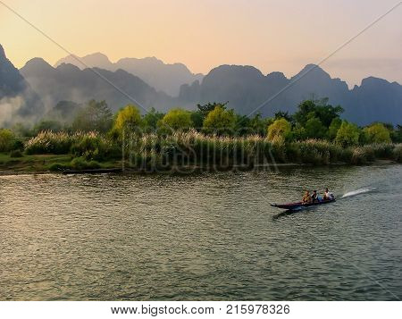 VANG VIENG LAOS - NOVEMBER 25: Motorboat moving on Nam Song River at sunset on November 25 2011 in Vang Vieng Laos. Vang Vieng is a popular destination for adventure tourism in a limestone karst landscape.