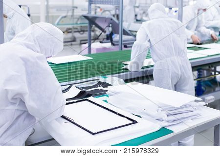 factory workers in white lab suits, producing tv sets on a green assembly line. some parts of a tv set are in the foreground.