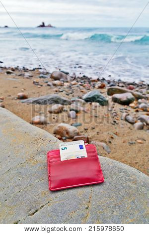 The lost purse on the seashore. The stony beach a small red purse with the note of five euros