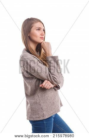 A young pretty girl, of European appearance, stands sideways and looks up with a pensive look and holds a hand to her chin. Isolated on white background.