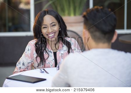 Black female disinterested with a blind date at an outdoor restaurant. They are sitting and chatting like speed dating. The image depicts relationship problems.