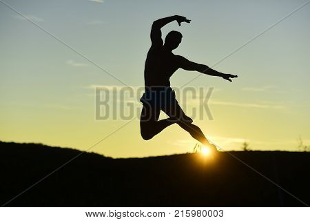 Sport and training concept. Silhouette of athlete jumping elegantly on sunset background copyspace. Sportsman trains dancing position in evening catching sun. Man with sportive figure practices sport
