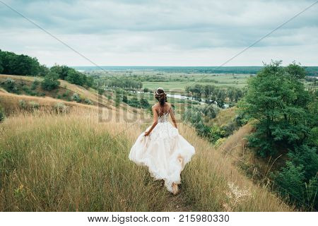 A Happy Bride Is Running In A Wedding Dress, Against A Backdrop Of Beautiful Nature.