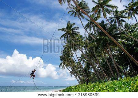 LAVENA FIJI - NOVEMBER 27: Unidentified boy swings on a rope swing on November 27 2013 in Lavena village on Teveuni island Fiji. Taveuni is the third largest island in Fiji.
