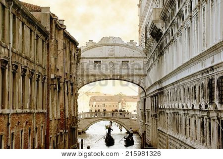 Venice Italy. April 21 2012: tourists taking a gondola boat trip at a channel and passing under the famous landmark The Bridge Of Sighs.