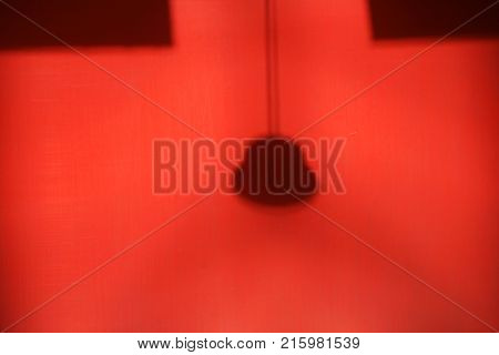 A lamp with lampshade and cable casts a shadow on a red wall.