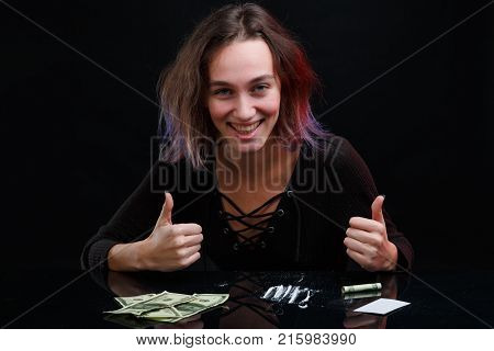 Happy young girl in black sweatshirt sits near dosed cocaine and dollar bills, smiling and showing thumb gesture up. On a black background.