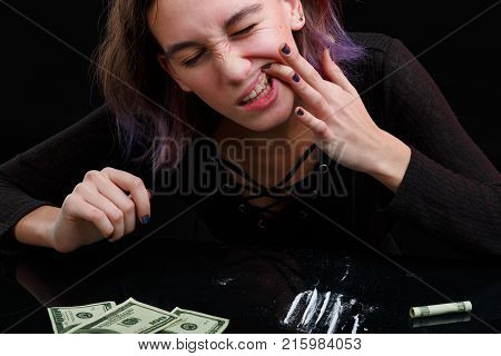 A young girl drug addict in a black sweater sits next to dosed cocaine and dollar bills and rubs cocaine into the gums. On a black background.
