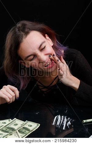 A young girl junkie rubs a white powder of cocaine into the gum, next to the dosed cocaine and a few dollar bills. On a black background.
