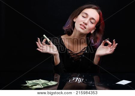 A drug-dependent young girl shut her eyes from the pleasure and holds in her hand a twisted dollar bill and a sharp blade next to the dispensed strips of cocaine. On a black background.