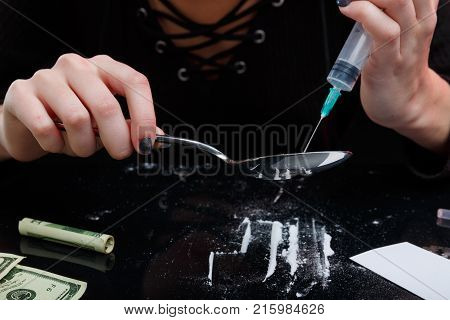 The hands of a drug-dependent girl pick up drugs from a spoon in a syringe. Next on the table is dosed white cocaine and a twisted dollar bill. On a black background.
